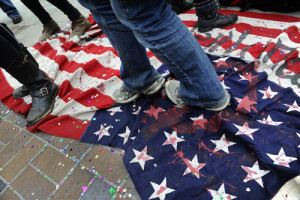 """Demonstrators dance on an American Flag during a weekly Occupy Denver protest at Civic Center. Earlier that day, protesters avoided interference at the Veterans Day parade and issued a statement that read; """"Occupy Denver supports the valor and sacrifice of the men and women of our armed forces, and unilaterally wishes to show unwavering support and respect for the Veterans Day Parade."""""""